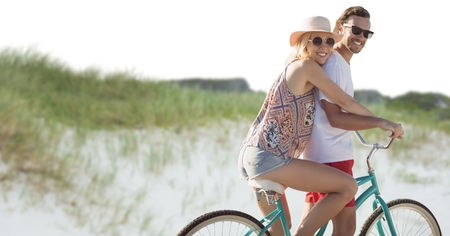 Digital composite of Millennial couple on bicycle against sand dune
