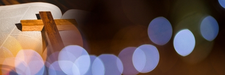 Digital composite of Cross on bible and brown and blue bokeh transition