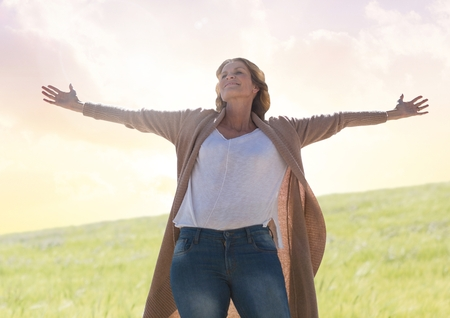 Digital composite of Woman practicing casual Mindfulness in front of nature field