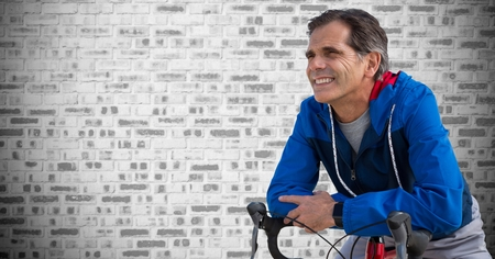 middle: Digital composite of Middle aged man on bicycle against grey brick wall