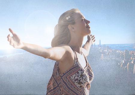 navigational light: Digital composite of Woman with open arms practicing casual mindfulness in front of city