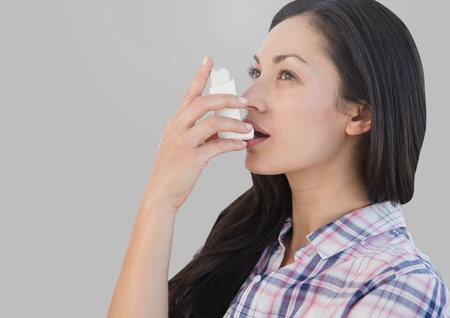Digital composite of Portrait of woman using asthma inhaler with grey background Stock Photo