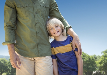 Digital composite of Father arm around son against sky and blurry trees Stock Photo