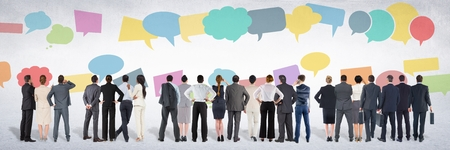 Digital composite of Group of business people standing in front of colorful chat bubbles
