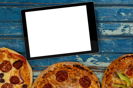Digital composite of Blank tablet device on table above three pizzas Stock Photo