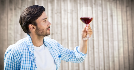 Digital composite of Man tasting wine against blurry wood panel Stock Photo