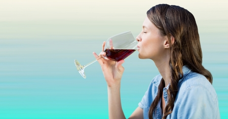 Digital composite of Woman tasting wine against light blue background Stock Photo