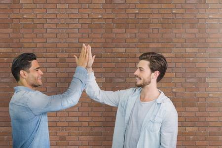 Digital Composite von Happy Business-Männer, die eine hohe fünf gegen Backsteinmauer Standard-Bild - 82452486