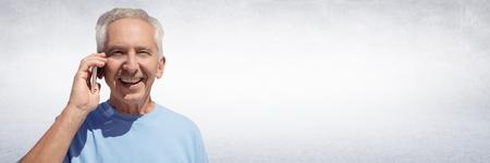 Digital composite of Elderly man on phone against white wall Stock Photo