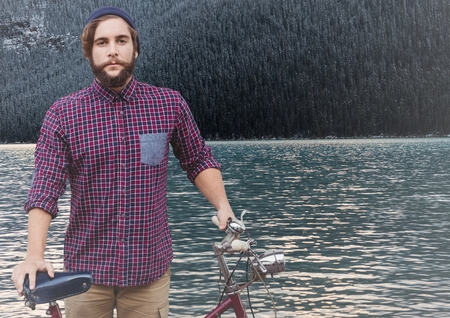 ripple: Digital composite of Millennial man with bicycle against river and forest Stock Photo