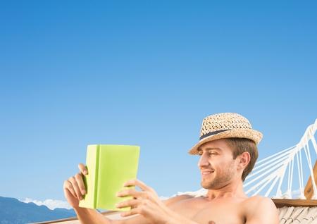 Digital composite of Man reading in hamoc against Summer sky