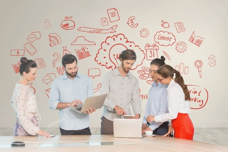 Digital composite of Business people at a desk looking at computers and tablets against white wall with red graphics Stock Photo