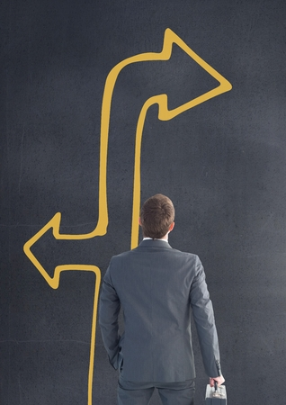 Digital composite of Business man looking up against grey background with yellow arrow Stock Photo
