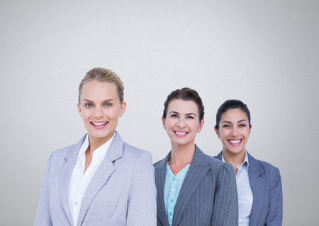 Digital composite of Group of businesswomen standing in front of grey background