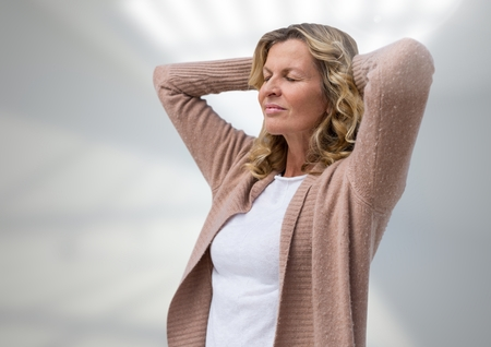 Digital composite of Woman practicing casual Mindfulness in front of blurred background Stock Photo