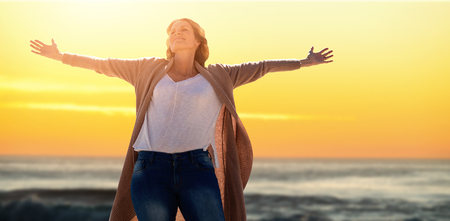 A woman raise her arms up against sunset over the waves