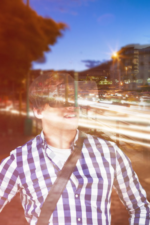 Young man with hand on hop wearing virtual reality simulator glasses against light trails on city street Stock Photo