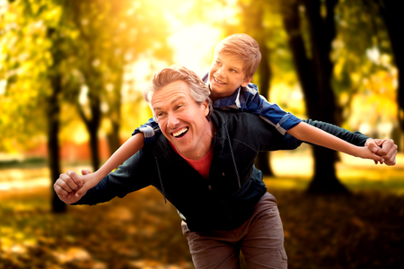 Father giving his son piggyback ride against defocused image of trees growing at park Stock Photo