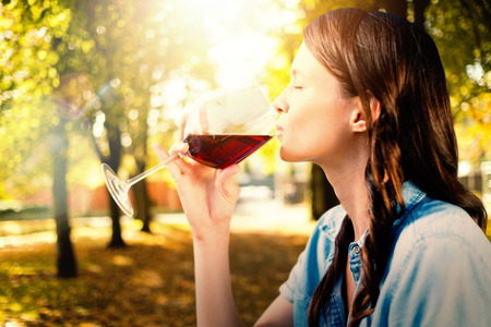 out of context: Woman drinking red wine against defocused image of trees growing at park