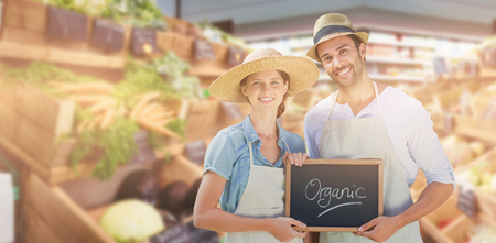 Portrait of smiling young couple holding writing slate together with organic text against vegetables in super market Stock Photo