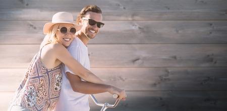 Nette Paare auf einem Fahrrad fahren digitales zusammengesetztes Bild gegen gebleichtes hölzernes Plankenhintergrund Standard-Bild