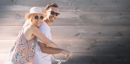 Cute couple on a bike ride digital composite image against bleached wooden planks background