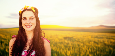 Beautiful woman with a flower crown against scenic view of wheat field