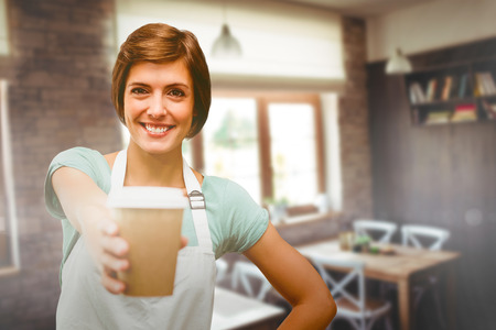 ceiling: Waitress pointing away a cup of coffee against empty chairs and tables Stock Photo