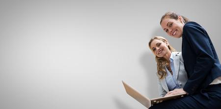 Portrait of business women posing with laptop against grey vignette