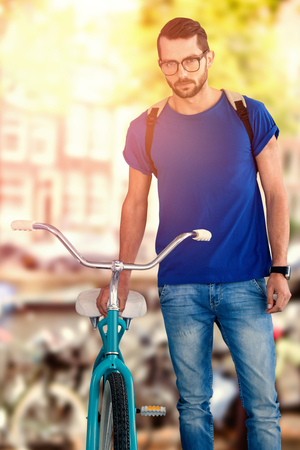 carrying: Full length of man with bicycle standing against white background against canal in amsterdam Stock Photo