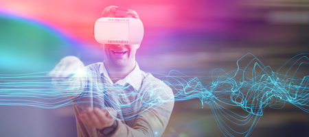 Happy man gesturing while using virtual reality glasses against futuristic glowing lines on black background Stock Photo