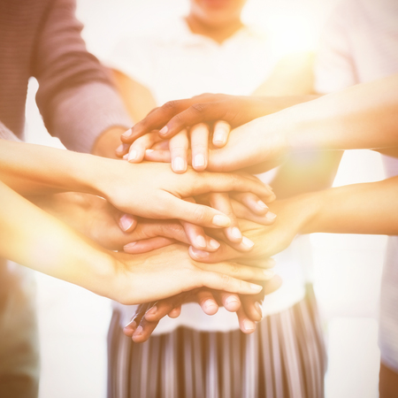 Close up of colleagues stacking hands while standing in office