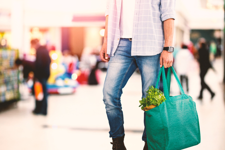 Low section of man holding bag with vegetables against interior of modern shopping mall