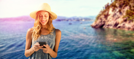 Beautiful woman using her mobile phone against idyllic view of sea
