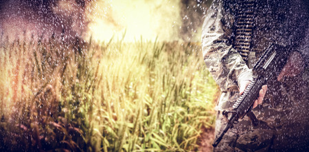 american field service: Empty path passing through fields against mid section of military soldier standing with a rifle