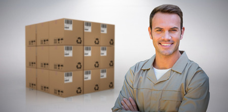 empty warehouse: Confident delivery man standing with arms crossed against grey background