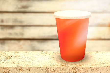 Red cup over white background against wood background