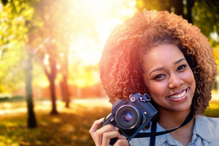 Headshot of smiling girl against defocused image of trees growing at park Stock Photo