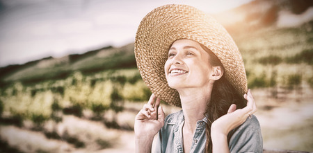 Happy woman wearing sun hat while looking away with vineyard in background