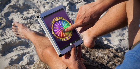 peace risk: Multi colored fortune of wheel on mobile display against man using digital tablet on the beach