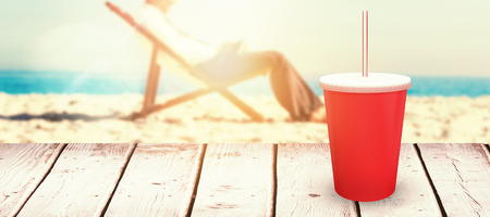 Young businessman resting on his deck chair using his tablet against red cup over white background