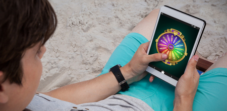 Wheel of fortune on mobile display against man using digital tablet on the beach Stock Photo