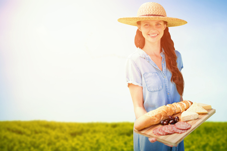 Smiling woman holding a food tray against flock of bird flying over field Stock Photo