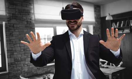 Smiling businessman using virtual reality glasses against empty chairs and tables 版權商用圖片