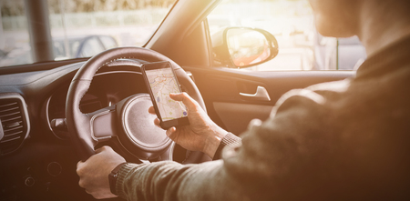 messy clothes: man looking at GPS on his phone inside his car Stock Photo