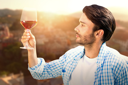 Man looking at glass of red wine against city landscape