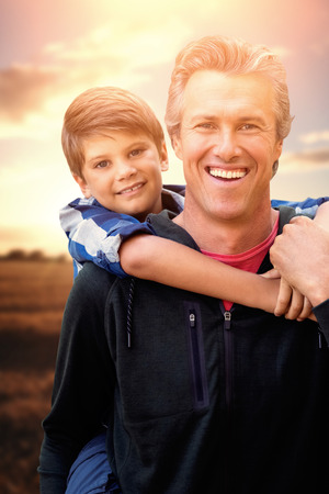 carrying: Father carrying his son on his shoulders against golden fields against cloudy sky