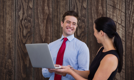 Businessman and businesswoman are holding a laptop against wood panelling Stock Photo