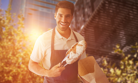 Baker packing loaf of bread against low angle view of modern buildings Stock Photo
