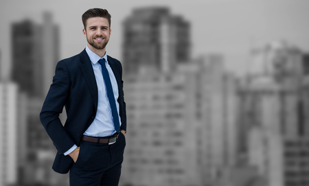 Portrait of businessman standing with hands in pockets against modern skyscrapers in city